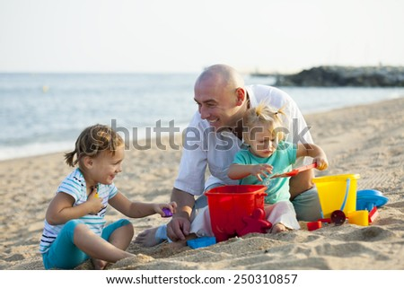 Happy little girls with dad playing at sea   - stock photo