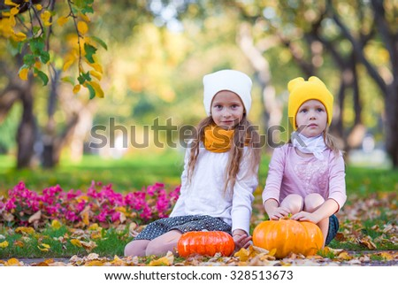 Happy little girls with pumpkins ready for Halloween outdoors at beautiful autumn day. Trick or treat - stock photo
