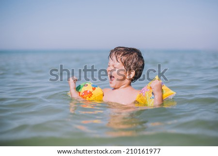 happy little happy boy playing at sea  - stock photo
