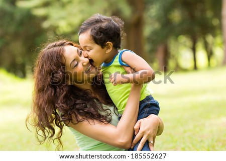 happy little indian boy kissing mother outdoors - stock photo