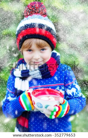 Happy little kid boy drinking hot cocoa and chocolate drink and marshmallows. Funny child in winter sweater, cap, long warm scarf and colorful gloves. On cold winter day during snowfall. - stock photo