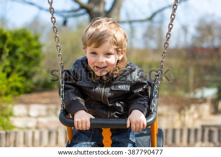 Happy little kid boy having fun on chain swing. Toddler child smiling and laughing on playground on spring day. - stock photo