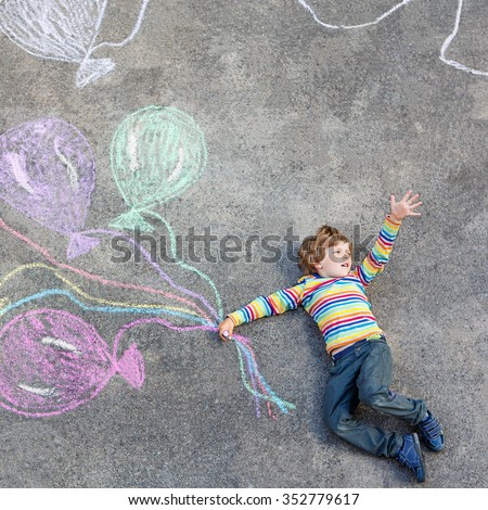 Happy little kid boy having fun with colorful balloons picture drawing with colorful chalks. Creative leisure for children outdoors in summer - stock photo