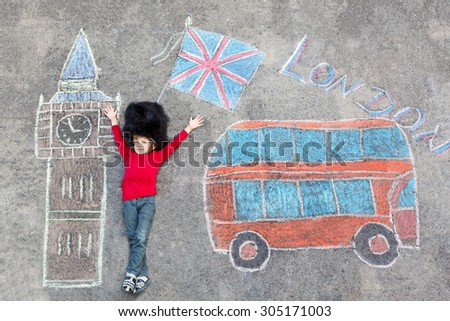 Happy little kid boy in british queen's guard soldier uniform having fun with London picture drawing with colorful chalks. With Big Ben, Union Jack and red bus. Creative leisure with children outdoors - stock photo