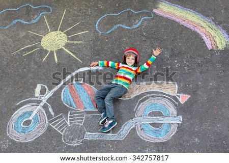 Happy little kid boy  in helmet having fun with motorcycle picture drawing with colorful chalks. Children, lifestyle, fun concept. child dreaming of future and profession. - stock photo