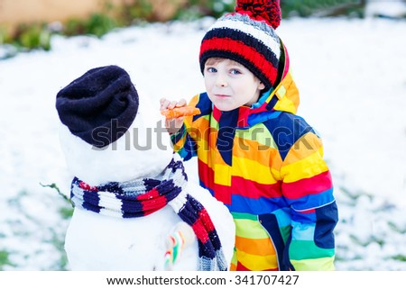 Happy little kid boy making a snowman and eating carrot. child playing and having fun with snow on cold day. Active outdoors leisure with kids in winter. - stock photo