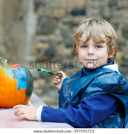 Happy little kid boy on a harvest festival, painting with colors a pumpkin. Child celebrating traditional festival halloween or thanksgiving. - stock photo