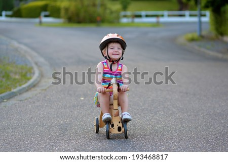 Happy little kid, cute blonde toddler girl in colorful dress and orange safety helmet playing outdoors on the street riding her push bike, wooden horse with three wheels, on a sunny summer day - stock photo