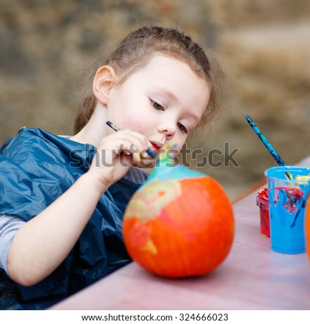 Happy little kid girl on a harvest festival, painting with colors a pumpkin. Child celebrating traditional festival halloween or thanksgiving. - stock photo