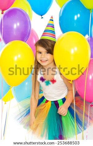 Happy little kid girl  with colorful balloons on birthday party. Holidays, birthday concept.  - stock photo