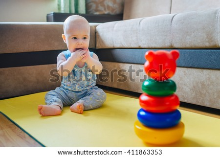 Happy little kid  playing with pyramid sitting on the floor - stock photo