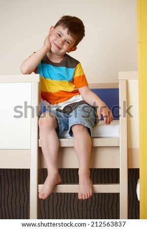 Happy little kid sitting on bunk bed, smiling. - stock photo
