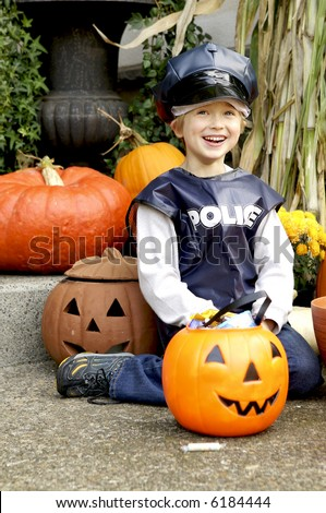 Happy little Policeman with a pumpkin full of candy - stock photo