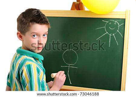 Happy little school boy drawing on a blackboard - stock photo