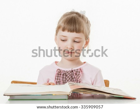 Happy little school girl learning to read, white background - stock photo