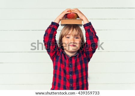 Happy little schoolboy with book and red apple on his head, wearing red and blue plaid shirt, standing against white wooden background. Back to school concept - stock photo