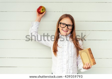 Happy little schoolgirl holding book and red apple, wearing white vintage blouse and black frame eyeglasses, standing against white wooden background. Back to school concept - stock photo