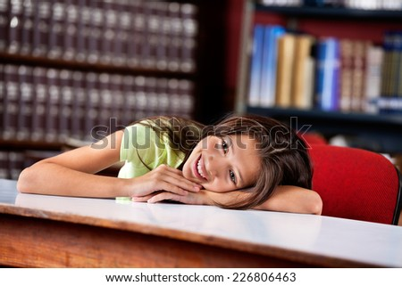 Happy little schoolgirl looking away while leaning on table in library - stock photo