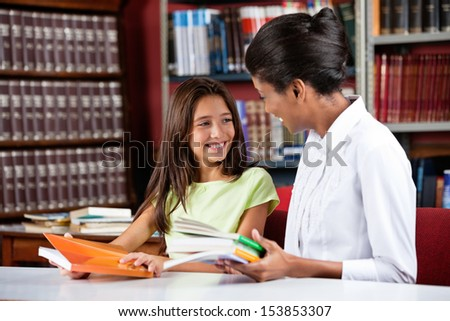 Happy little schoolgirl looking female librarian while sitting with books at table in library - stock photo