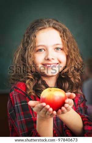 Happy little schoolgirl with apple  - portrait in classroom - stock photo
