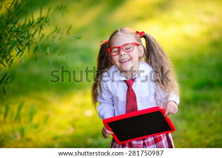 Happy little schoolgirl with chalkboard going back to school outdoor - stock photo
