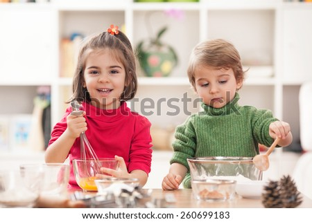 Happy little sister and brother baking together in the kitchen - stock photo