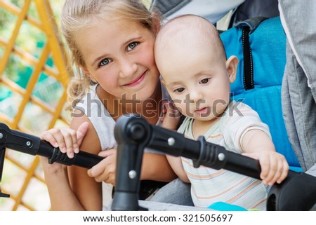 Happy little sister hugging baby brother in a stroller - stock photo