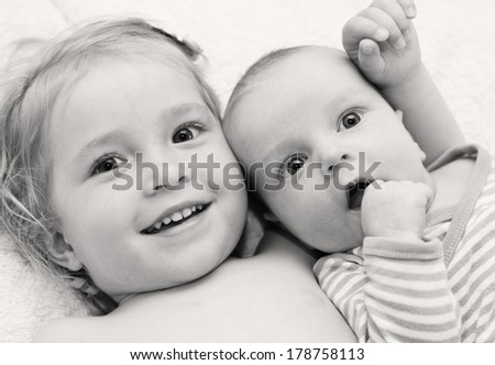 happy little sister hugging her brother lying on a white blanket ( black and white ) - stock photo