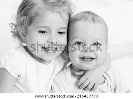 happy little sister hugging her brother on a white background ( black and white ) - stock photo
