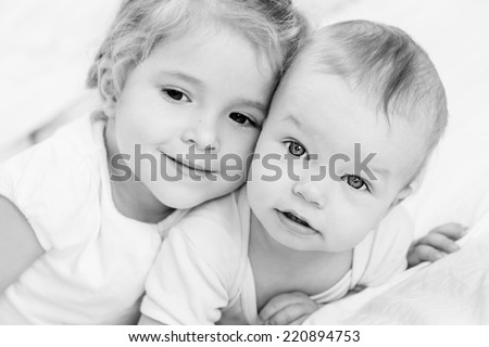 happy little sister hugging her brother on a white background ( focus on one child ) (black and white) - stock photo