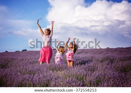 Happy little sisters with their mother are in a lavender field holding bouquet of purple flowers - stock photo