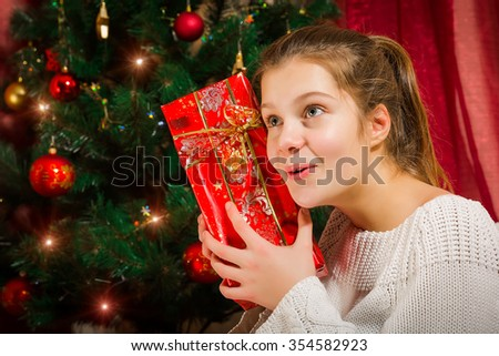 Happy little smiling and surprised girl with christmas gift box. - stock photo