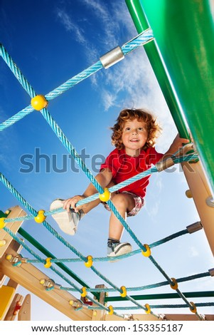 Happy little smiling three years old child boy climbing on the playground ropes with sky on background - stock photo
