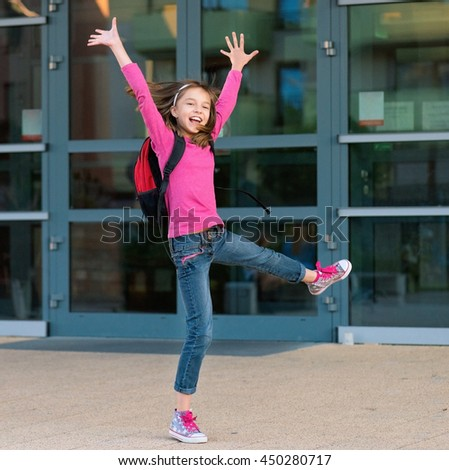 Happy little student with backpack excited to be back to school. Beginning of class after vacation. Full length outdoor portrait. - stock photo
