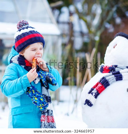 Happy little toddler boy making a snowman and eating carrot, playing and having fun with snow, outdoors  on cold day. Active outdoors leisure with kids in winter. - stock photo