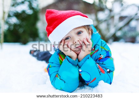 Happy little toddler boy waiting for Christmas santa hat, laying on snow in winter garden, outdoors. - stock photo