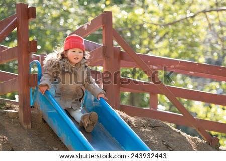 Happy little toddler girl having fun sliding on playground  - stock photo