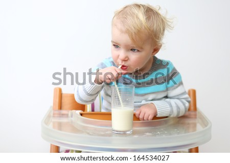 Happy little toddler girl in blue stripes sweater drinking milk from the glass with straw sitting indoors in high feeding chair against white wall - stock photo