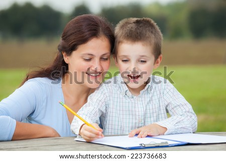 Happy little young boy in white shirt and his smiling mother write or draw with a pencil on a sheet of paper on wood table in the park  - stock photo