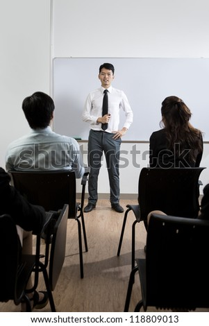 Happy looking Chinese Business man giving presentation - stock photo
