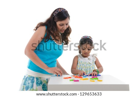 happy looking indian mother and daughter learning with educational toy - stock photo