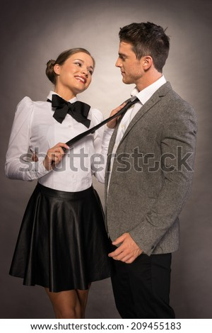 Happy Lovely Couple in Trendy Attire Isolated Gray. Lady Emphasizes Fixing Mans Neck Tie While Holding to Her. - stock photo