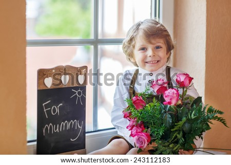 Happy lovely smiling little kid boy with blooming pink roses in bunch and blackboard, congratulating his mum for mother's day. - stock photo