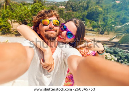 Happy lovers,  attractive woman and man traveling  in tropical island enjoying romance.  Attractive couple  making selfie, smiling and have fun together. - stock photo