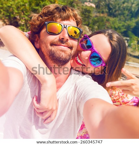 Happy lovers, woman and man traveling on vacation travel in tropical island enjoying romance.  Attractive couple  making selfie, smiling and have fun together. Instagram filter. - stock photo