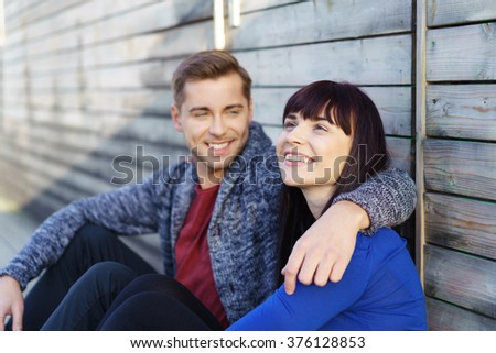 Happy loving attractive young couple sitting arm in arm leaning against an old wooden wall smiling with pleasure - young woman with a dreamy faraway look - stock photo