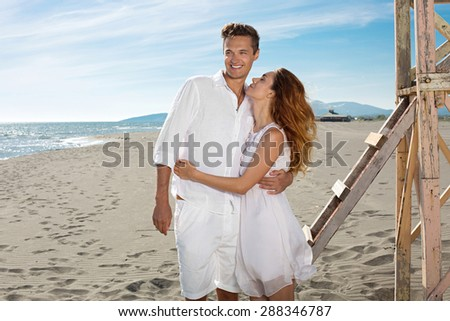 Happy loving couple at white clothes enjoy a hot summer day on a beach near the lifeguard tower - stock photo