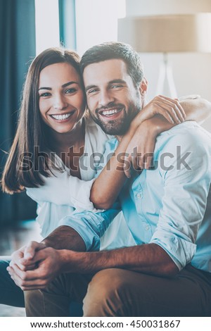 Happy loving couple. Beautiful young loving couple sitting together on the couch while woman embracing her boyfriend and smiling - stock photo