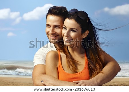 Happy loving couple embracing on the beach, smiling, looking away. - stock photo