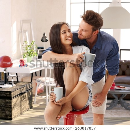 Happy loving couple embracing, smiling at home. - stock photo